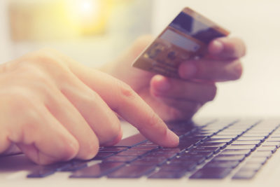 A hand holds a credit card, while the other hand types the numbers into an e-commerce site
