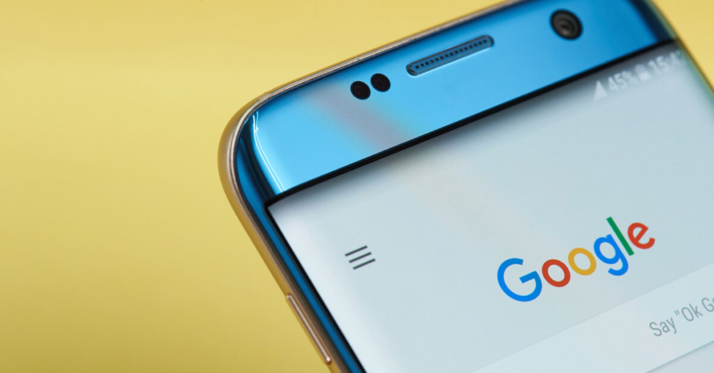 A blue smart phone showing the Google search home page, with a bright yellow background behind it